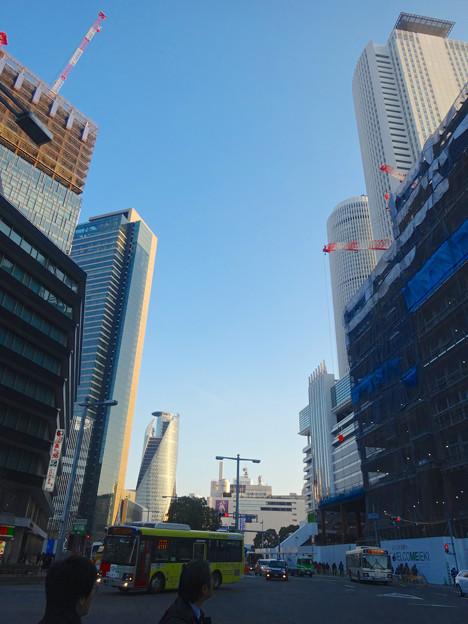 写真: 夕暮れ時、名駅でビル群を見上げる